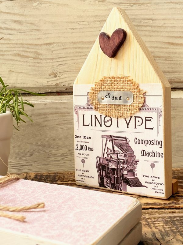 mini wood house with old linotype ad and wooden heart